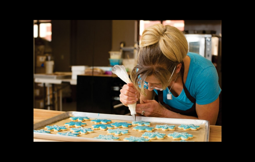 Sarah Niebler decorates snowflake cookies at Sunshine & Moons organic bakery