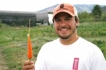 Chef Nate King holds up carrot at Rendezvous Farm