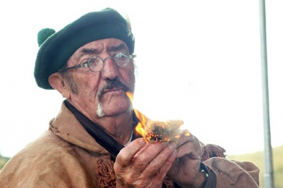 A Craig sheepherder ignites hemp, traditionally used for making cooking fires